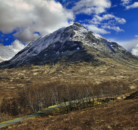 midday: Glen Etive Higland Scotland. Sunny over midday. Snow covered mountain.
