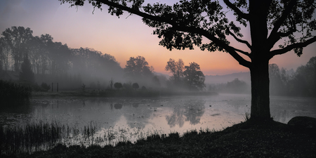 Sunrise over quiet pond. Cold morning october fog.