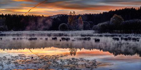 Beautiful sunrise over quiet lake. October morning near Vilnius, Lithuania