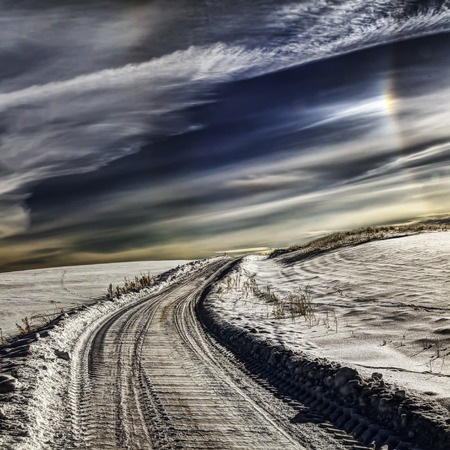 Village road in winter. Very cold weather, cloudscape and sun halo in sky.