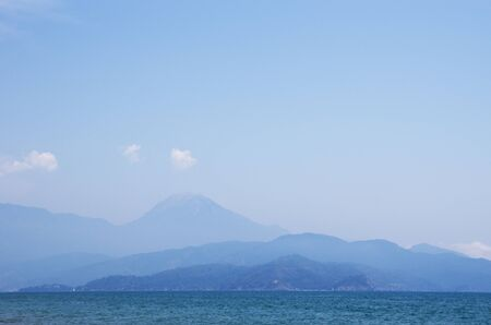 Off shore mountains in haze Stock Photo