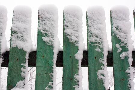 Wooden fence away in to snow