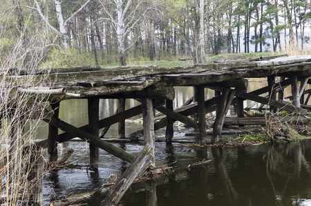Old wooden bridge over the river in spring Stock Photo