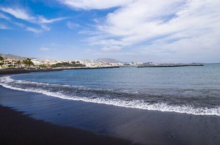 Black lava sand beach on the coast of tenerife Archivio Fotografico - 132073926