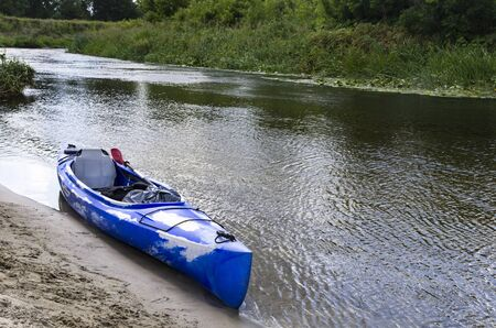 Kayak by the sandy bank of the river Archivio Fotografico - 132363543