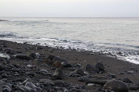Black lava stones in the surf