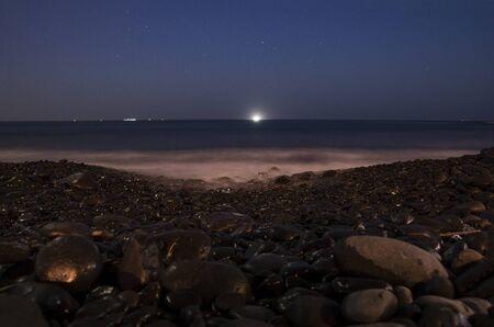 Night landscape of the sea coast with black pebbles Archivio Fotografico