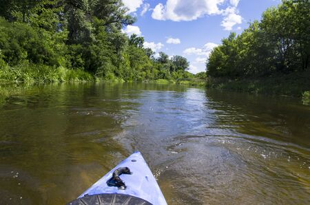 Kayak feed on a river with overgrown banks Archivio Fotografico