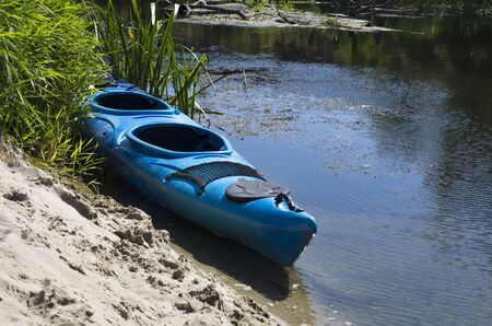 Kayak on the sandy shore of a small river