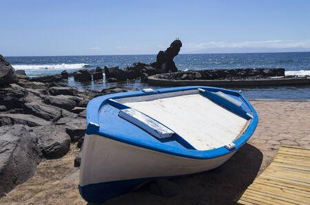 Wooden boat on a stone seashore Archivio Fotografico