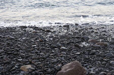 Sea surf on a black volcanic beach