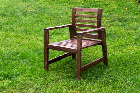 One wooden chair on green grass