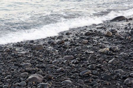 Volcanic pebbles on the surf line in black