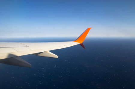 Airplane wing flying over the ocean Archivio Fotografico