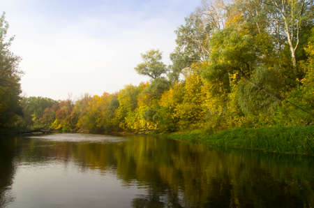 Autumn river landscape with trees on the bank