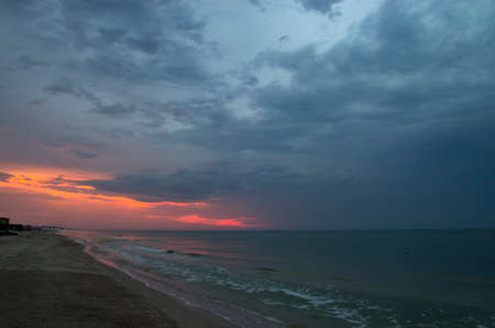 Sunset over the sea in cloudy weather, landscape
