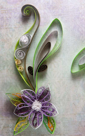 Quilling in the form of a flower on background paper