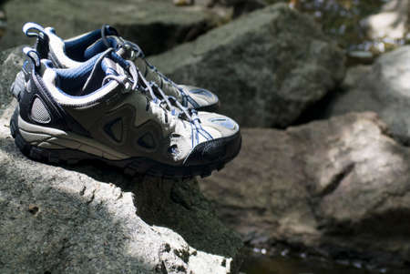 A pair of hiking shoes stand on granite stones Archivio Fotografico