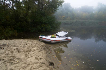 Inflatable boat on the bank of a misty river in autumn