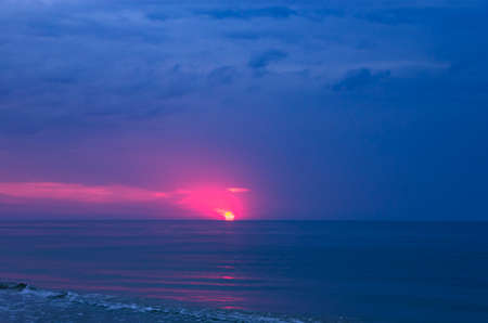 Colorful sunrise with sun on cloudy sea Archivio Fotografico
