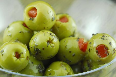 green olives stuffed with pimento and spiced with basil and olive oil photo