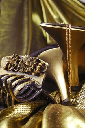 golden womans shoes and golden accessories photo