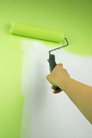 hand schilderen: hand schilderij muur met roll in groene kleur Stockfoto