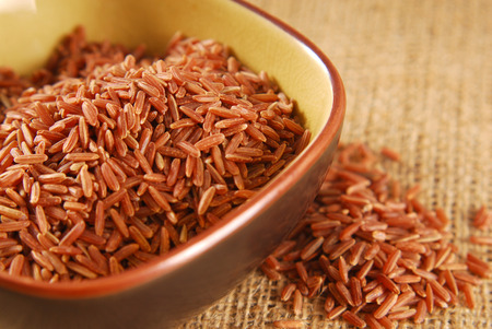 wild rice: red rice in bowl on hessian fabric