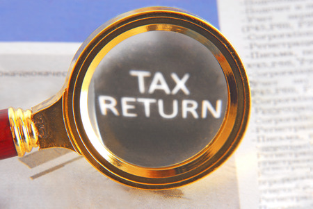 tax forms: tax return and magnifying glass
