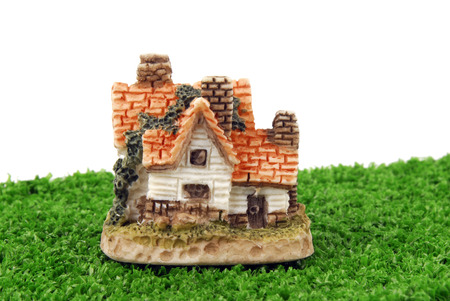 miniature house on green grass isolated on white