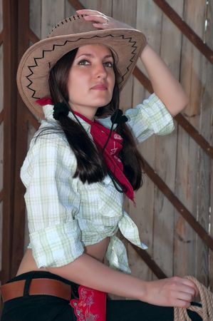 cute young farm girl: girl in a cowboy hat sitting on a background of wooden gates Stock Photo