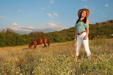girl cowboy standing in a field with a horse photo