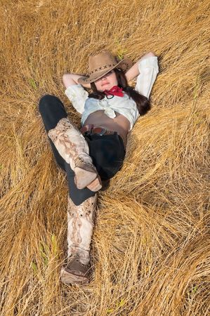 cowboy girl lying in a field of grass photo