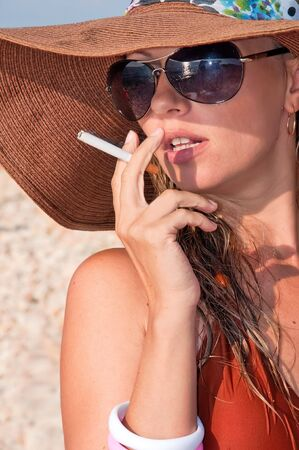 attractive woman in a hat smoking a cigarette photo