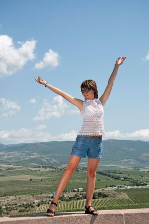 girl is standing with hands up against the background of beautiful scenery photo