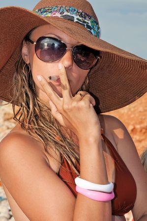 attractive woman in a hat smoking a cigarette in bikini photo