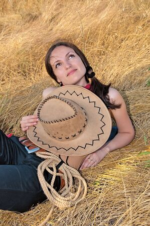 beautiful woman lying in the straw with the hat photo