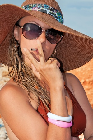 beautiful woman smokes a cigarette on the beach photo