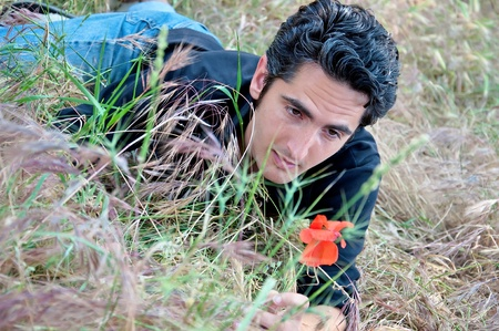 young man, lying on the grass looking at flower photo