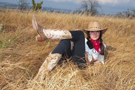 Woman cowboy relax on the straw in a field  photo
