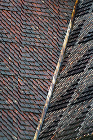 Creatively constructed Roof with rectangular wooden roof tiles shingles on old conservation building in Sweden. Concept of using old techniques on new buildings and Scandinavian Pattern.