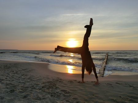 handstand: Woman doing a handstand at the Baltic Sea during sunset Stock Photo