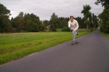 man pushing: Man pushing longboard on a street