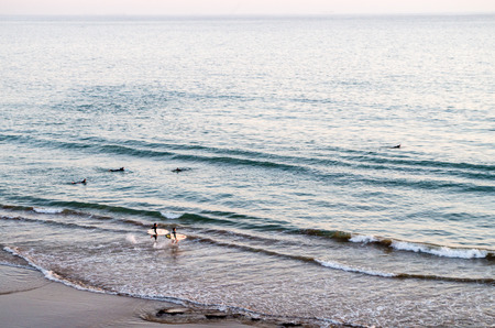 Surfers running into the water with their surfboards