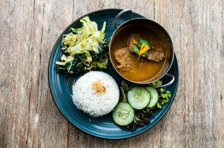 Tyical Indonesian dish: Rendang beef served with vegetables and rice