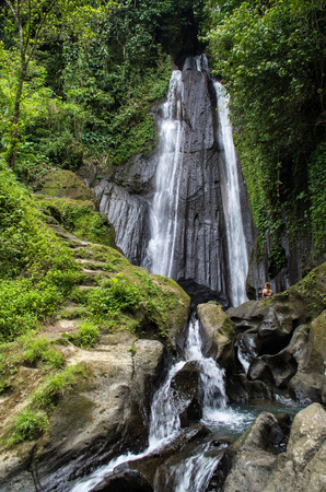 Dusun Kuning waterfall in Bali with woman looking at it