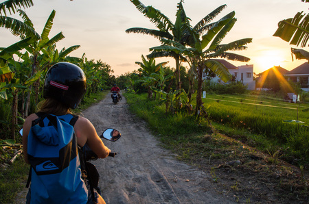 Woman drives with scooter along a smaller road in the Canggu area, Bali, Indonesia, January 2017.