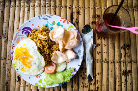 Typical Indonesian dish mie goreng with drink.