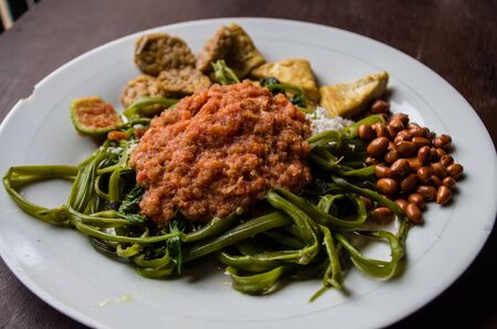 Indonesian dish kankung plecing (spicy water spinach dish) typical for Lombok island close up. Stock Photo