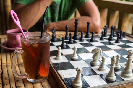 Glass of ice tea and coffee while playing chess.